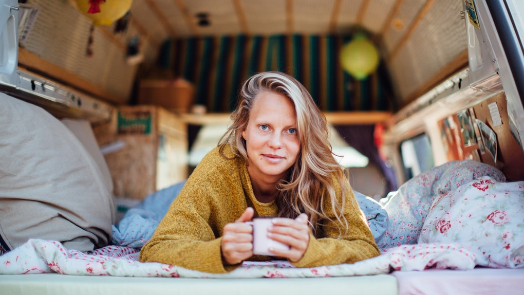 A blonde woman wearing a sweater lays down in her camper van while holding a mug of coffee.