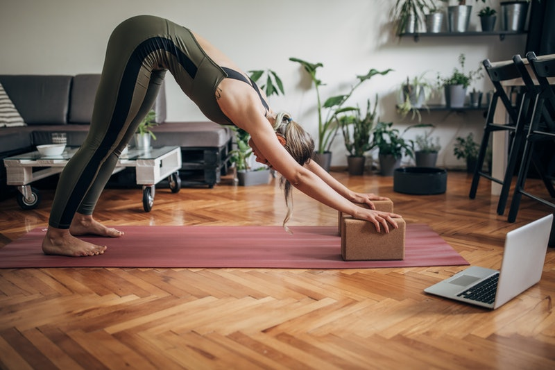 A person holds a plank on her yoga mat at home. Knowing how to modify yoga poses for your own body c...