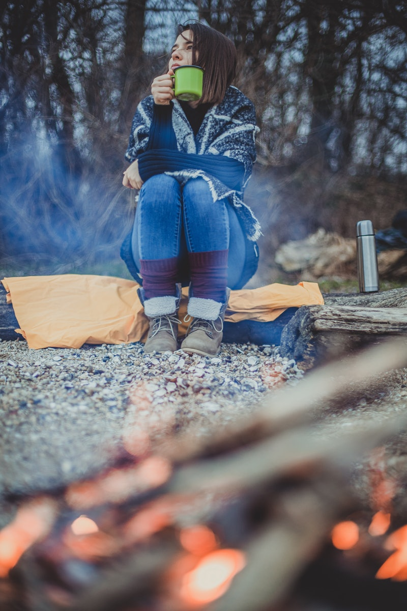 A woman sits in front of a campfire with a mug of tea. If you get the winter blues, a therapist explains how to prepare for seasonal affective disorder starting now.