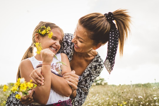 mom and daughter hugging in a field