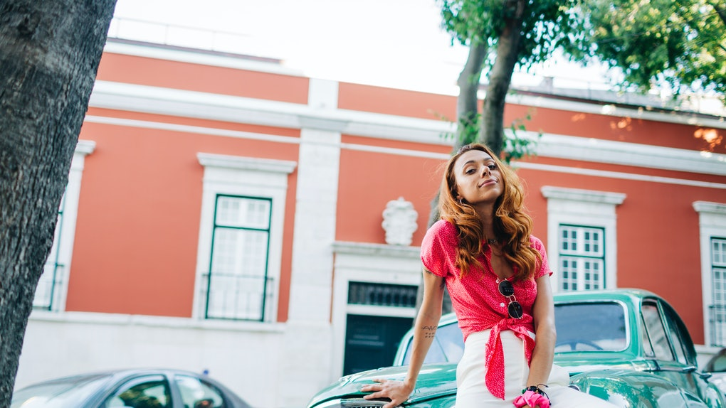 A young woman poses against a teal classic car that's parked in the road while wearing a hot pink blouse.