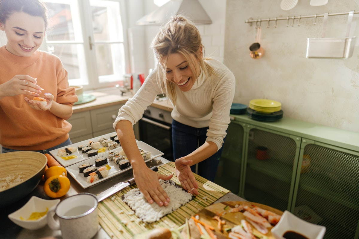 Friends make some sushi rolls in their kitchen together.