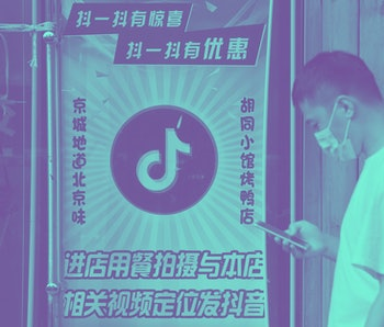 A man wearing a face mask can be seen on his smartphone while passing by a poster for TikTok.