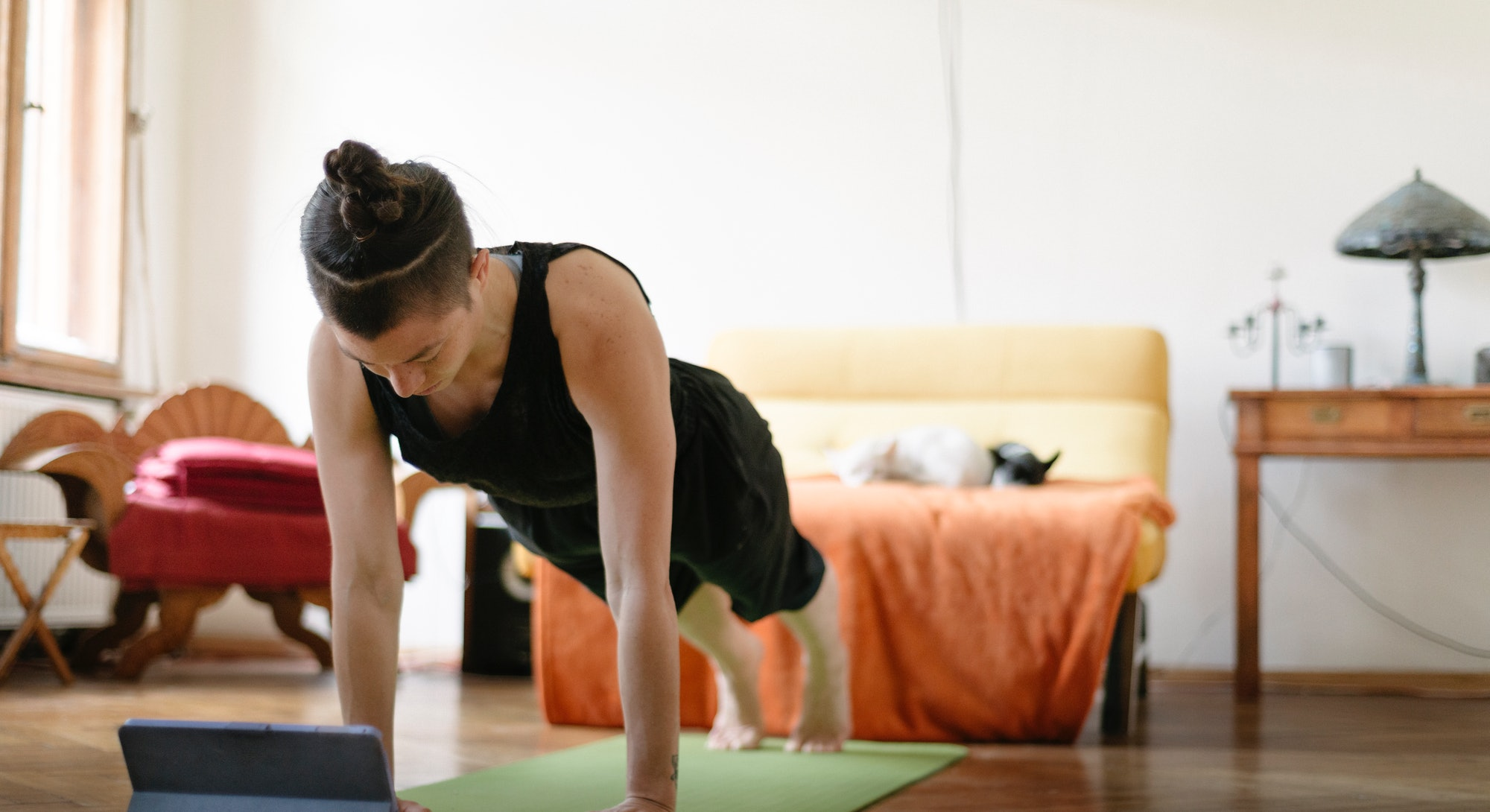 A woman works out watching a video on her iPad. Apple launched Fitness+, a new virtual streaming workout service for Apple Watch.