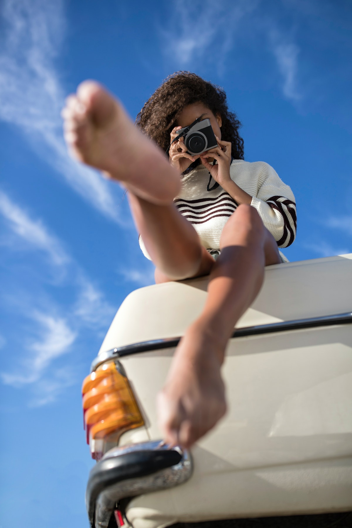 A young Black woman sits on the trunk of a vintage car and takes a photo on a vintage camera.