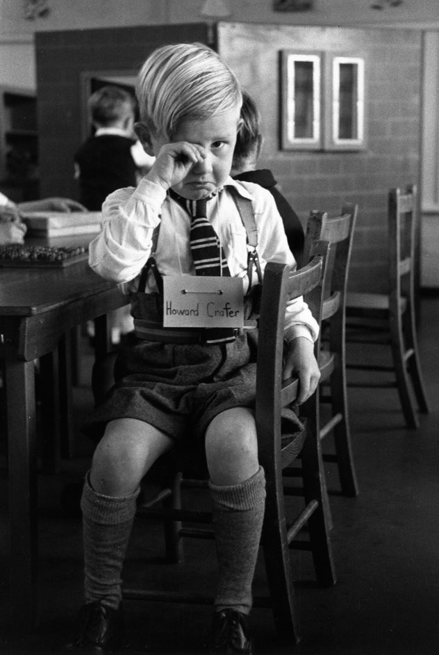 This vintage back to school photo shows a little boy upset on his first day of school.