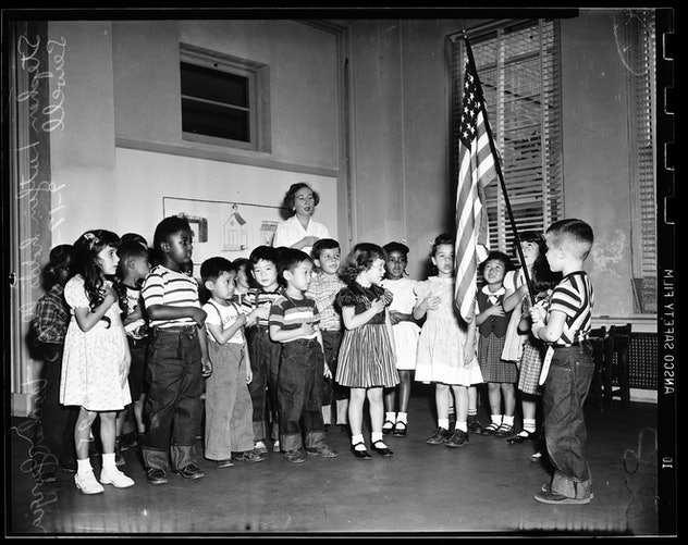 This vintage back to school photo shows a group of children reciting The Pledge Of Allegiance.