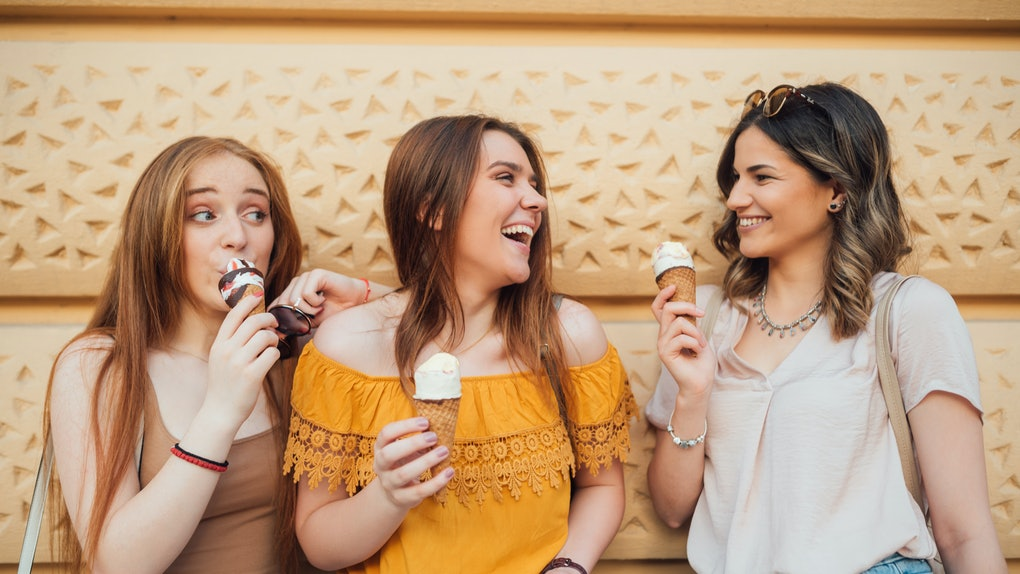Three happy women eat ice cream and laugh while leaning against a wall.