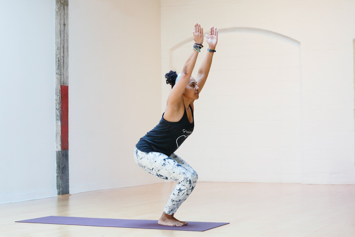 A person with natural hair and patterned yoga pants sinks into chair pose. Chair pose builds core st...