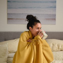 A woman in a yellow blanket drinks tea. Here's what happens to your body when you stop drinking alcohol.