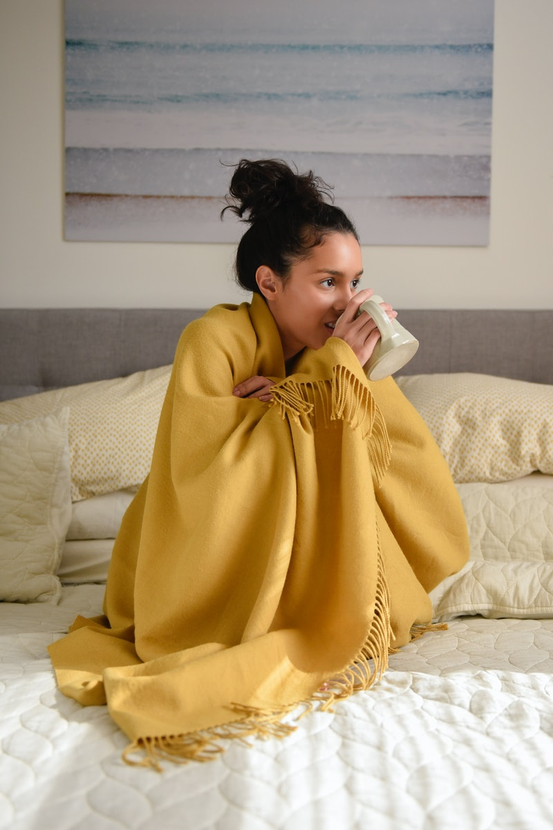 A woman in a yellow blanket drinks tea. Here's what happens to your body when you stop drinking alco...