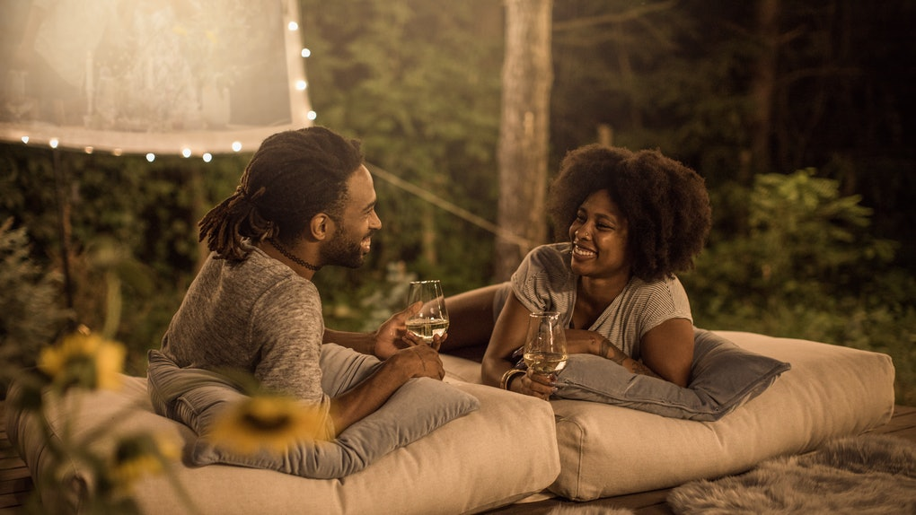 A happy couple leans on pillows and holds wine glasses in their backyard while watching a movie.