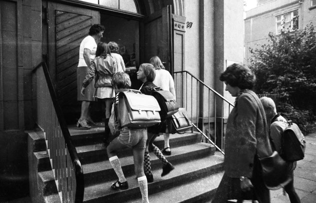 Kids are walking up to the school doors in this vintage back to school photo.