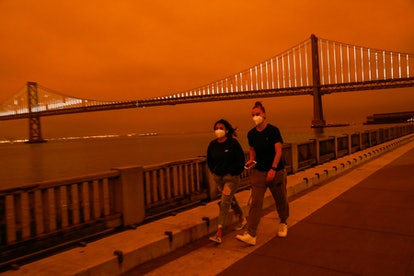 Two people walk in San Francisco through wildfire smoke. Smoke from wildfires can harm your health.