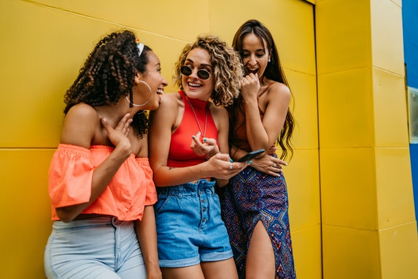 Three friends laugh at something on their phone, while leaning against a yellow building.