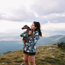 A woman hiking holds up a dog. Here's how getting a dog changes your brain