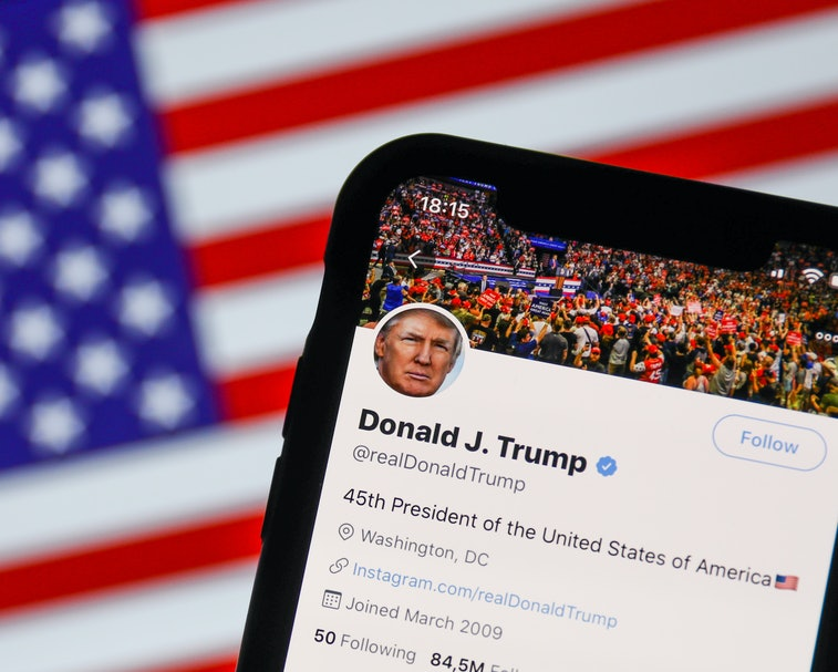 The official Twitter account for Donald Trump is seen in front of the American flag.