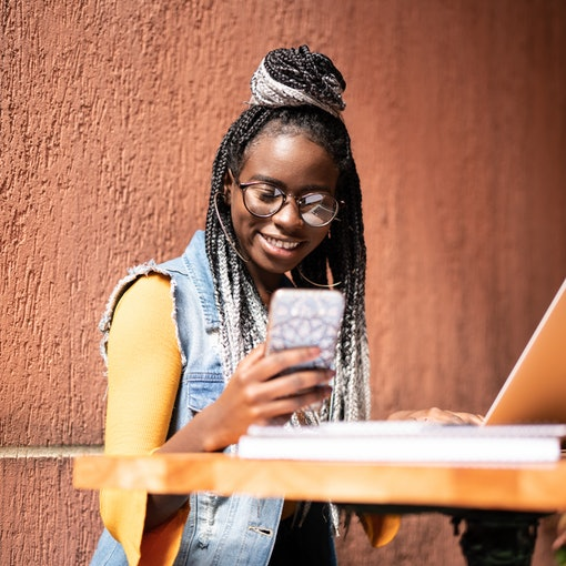 A happy woman wearing a denim vest and glasses texts while sitting at a table with her laptop outside.