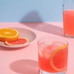A pink grapefruit and orange cocktail against a pink and blue background. Alcohol can negatively affect your health in myriad ways; doctors explain 7.