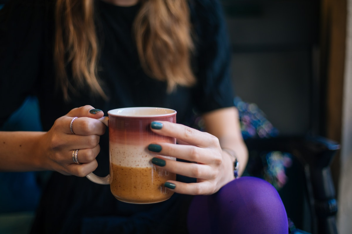 A woman with dark nails drinks tea indoors. Fall and winter pandemic hobbies can be boons during the cold months.