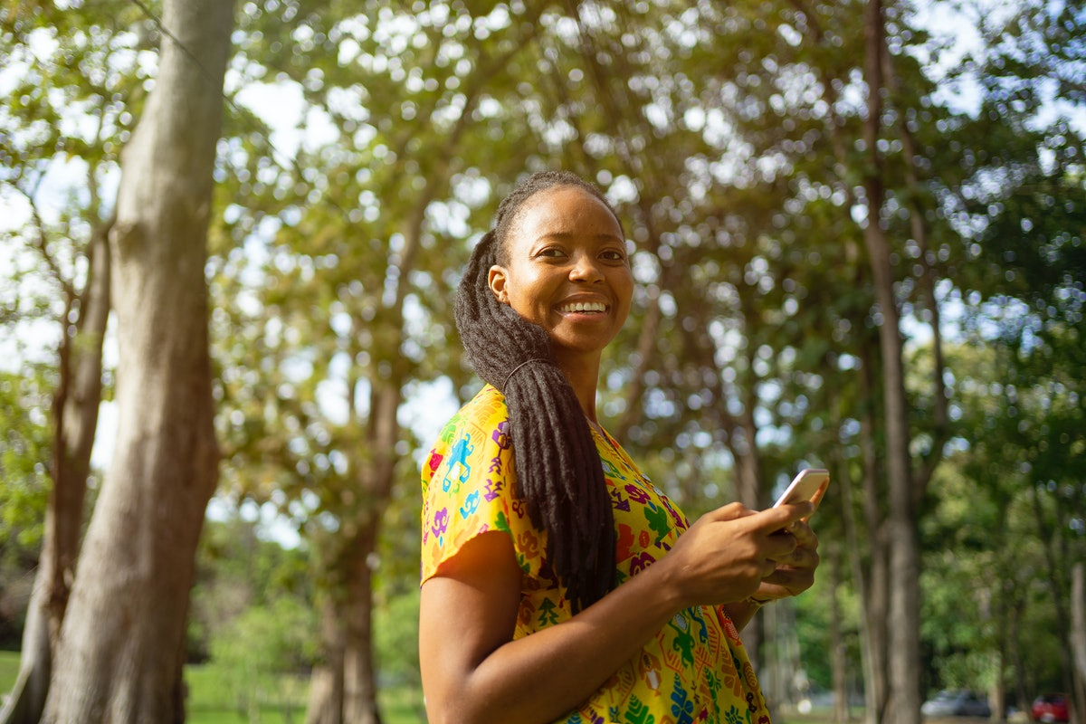 A young Black woman smiles while standing amongst green trees and typing on her phone.