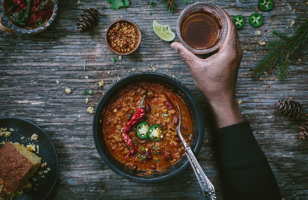 A bowl of turkey chili sits on a wooden table next to a refreshing drink.