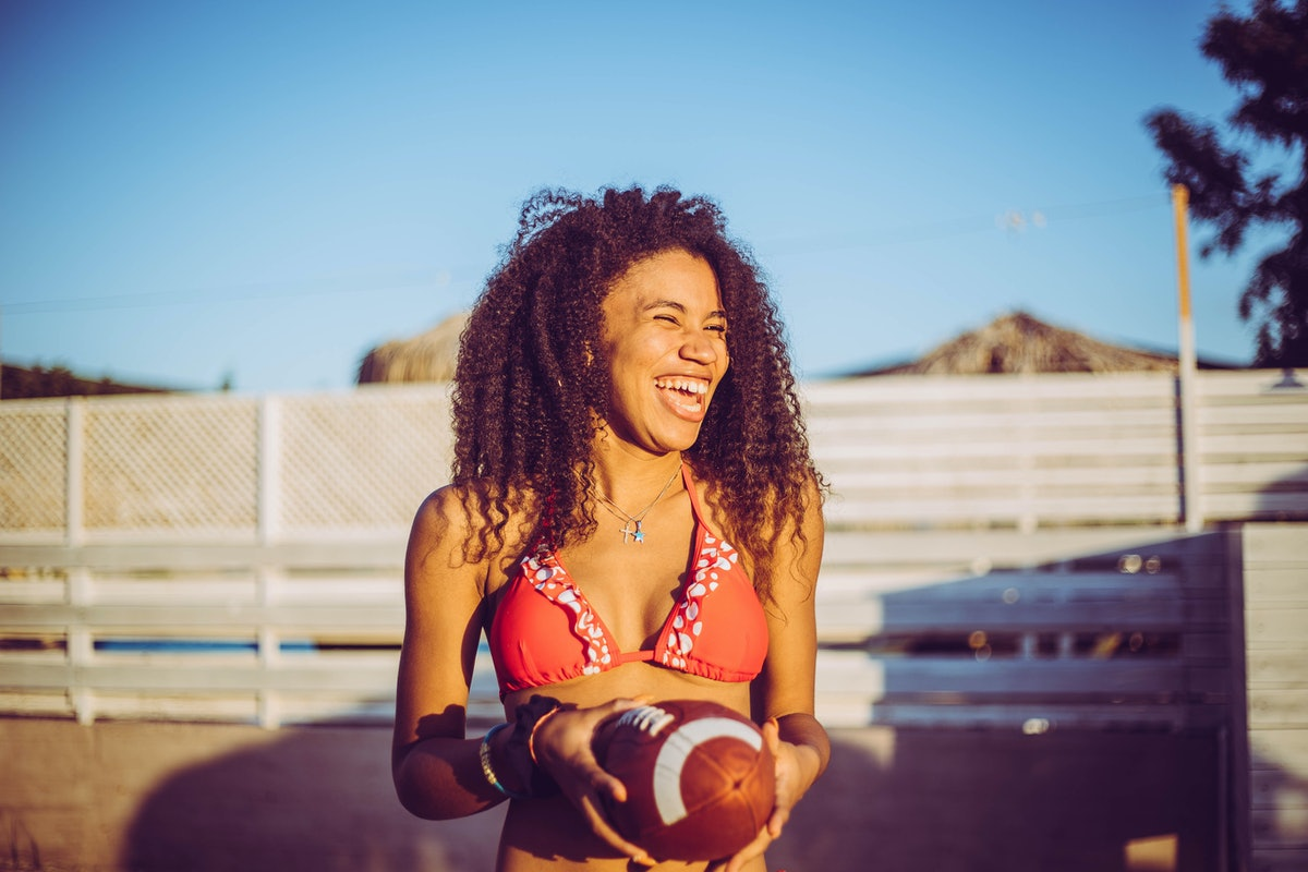 A happy woman in a bikini top holds a football outside at sunset.