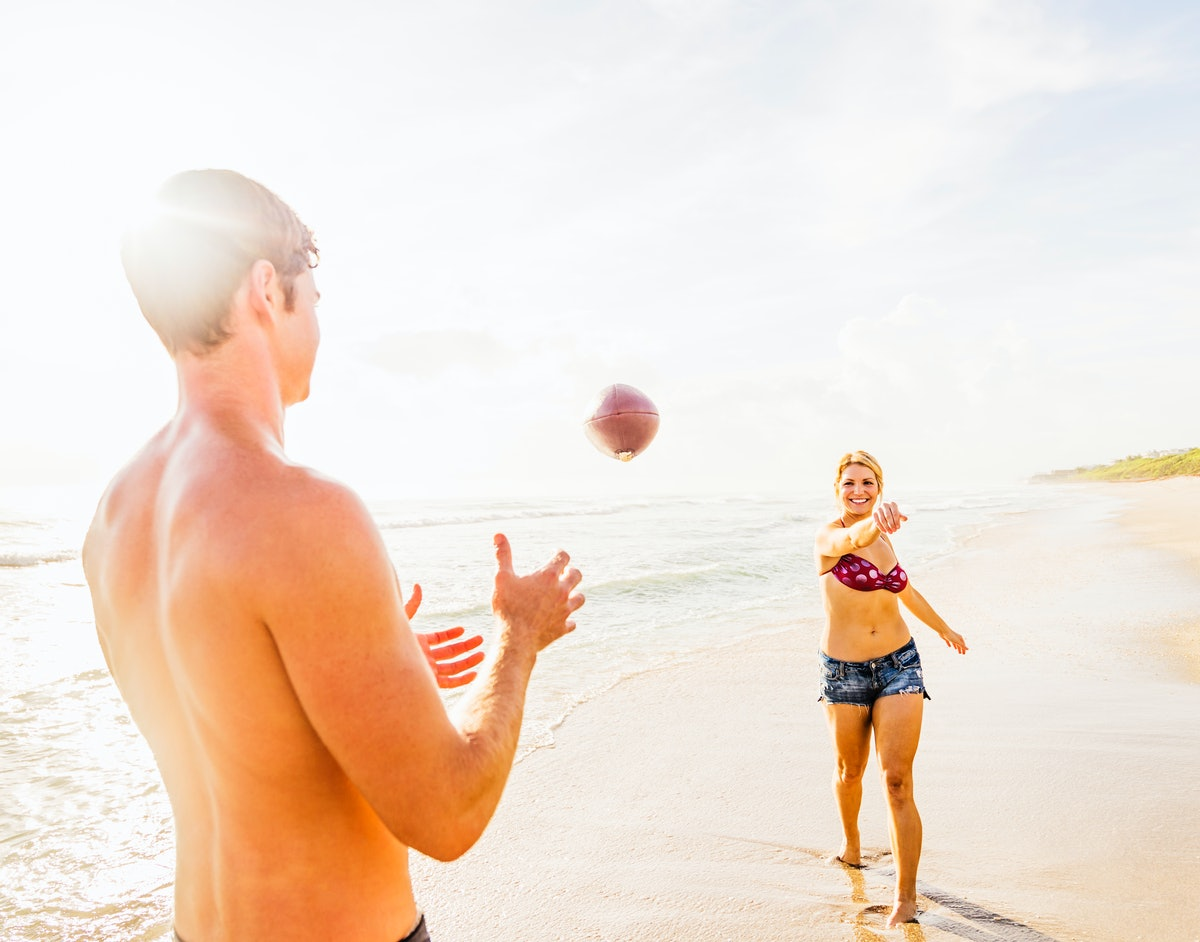 A blonde woman in a bikini top and denim shorts tosses a football to her boyfriend at the beach.