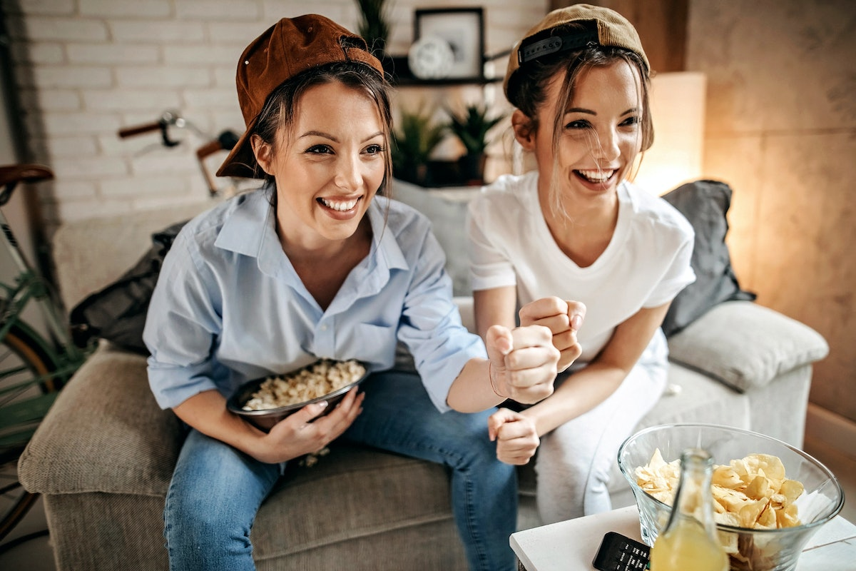 Two sisters wearing backwards baseball caps watch TV while sitting on a couch and smiling.