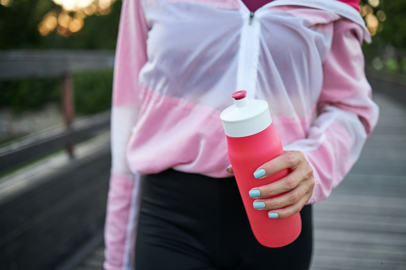 A woman holds a water bottle during a run. These dumbbell alternatives make great at home workouts while dumbbells are sold out.