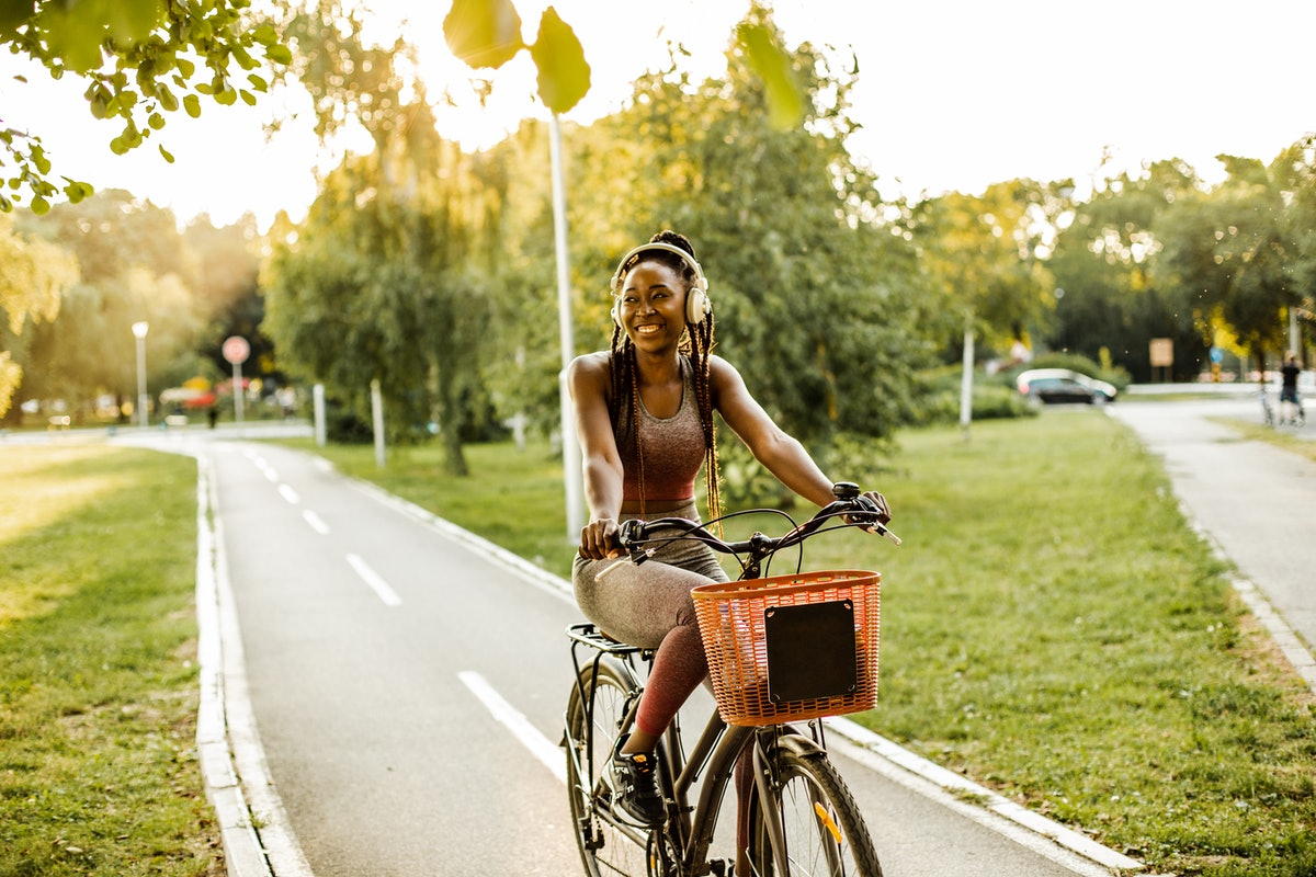 A young Black woman rides her bike on a paved trail while wearing headphones and smiling.