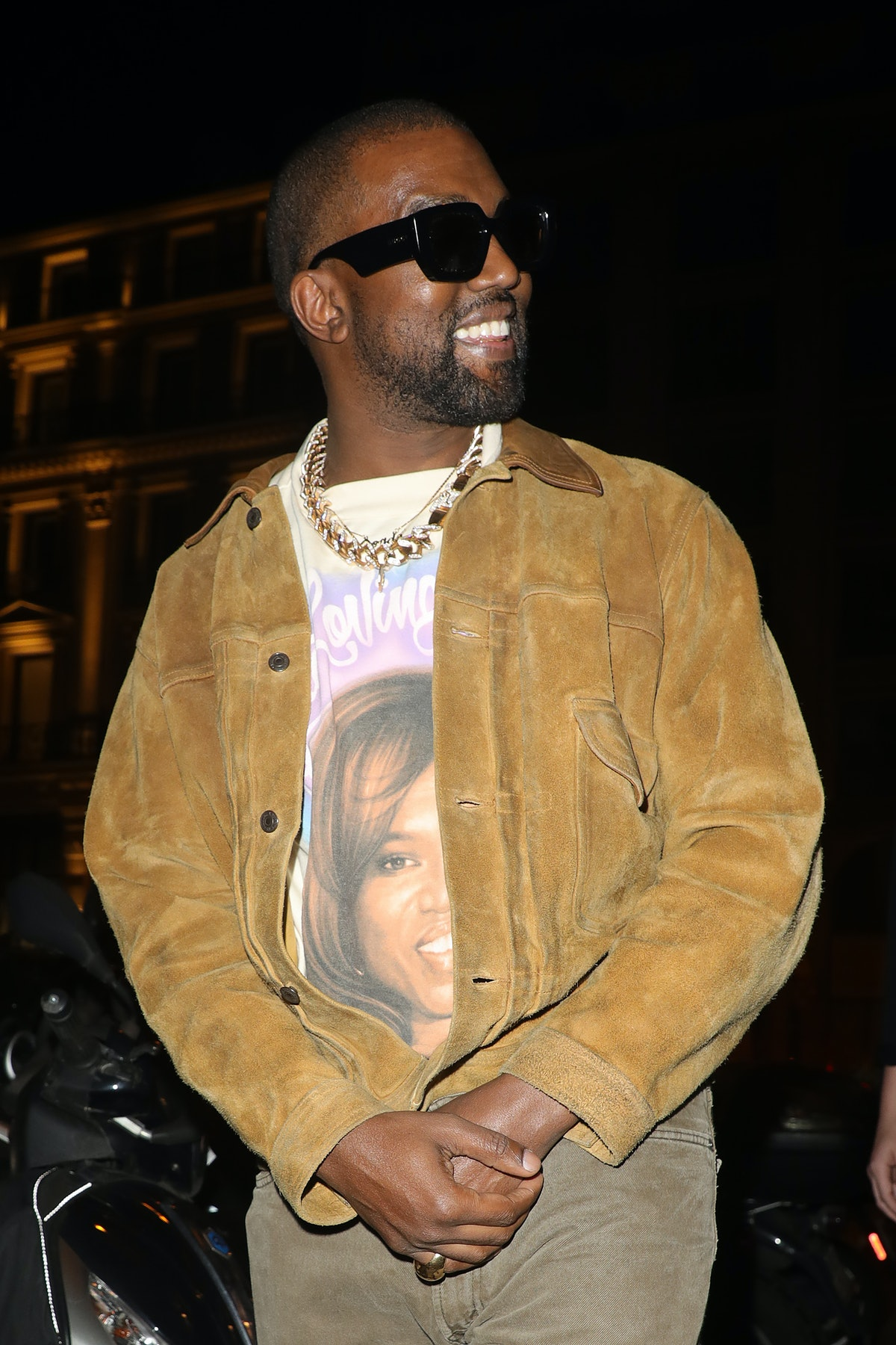 Kanye West steps out in a brown suede jacket and black shades.