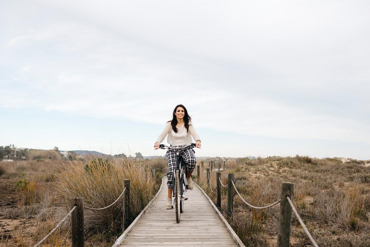 A young woman bikes down a tiny boardwalk near the beach.