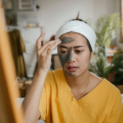 A woman applies a facemask while hungover. How does a hangover affect your body? Doctors have answers.
