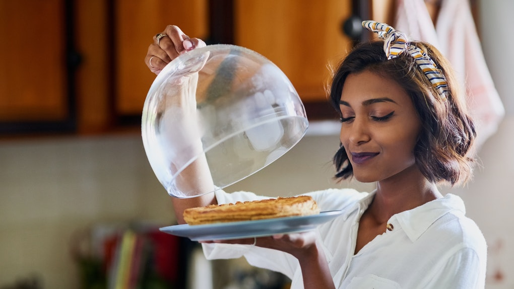 A woman removes the cover from a pie to smell it in the kitchen.