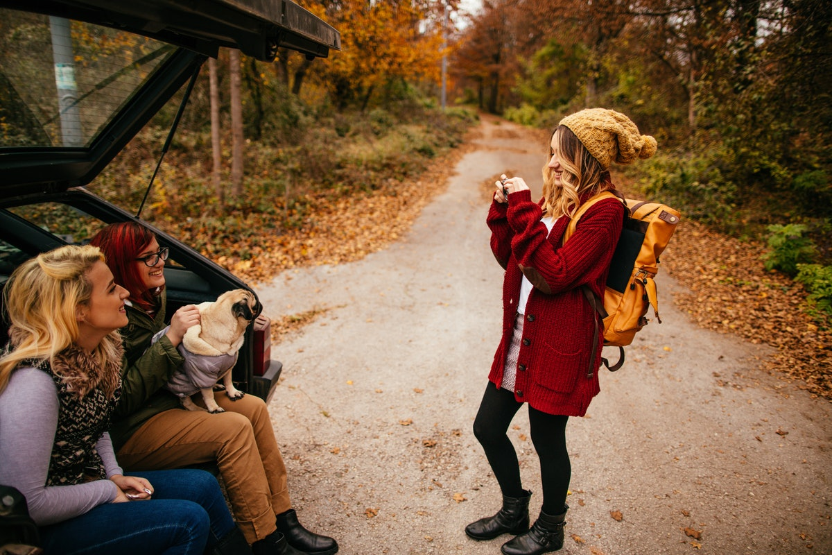 A woman takes a picture of her friends in the back of their car on a fall road trip.