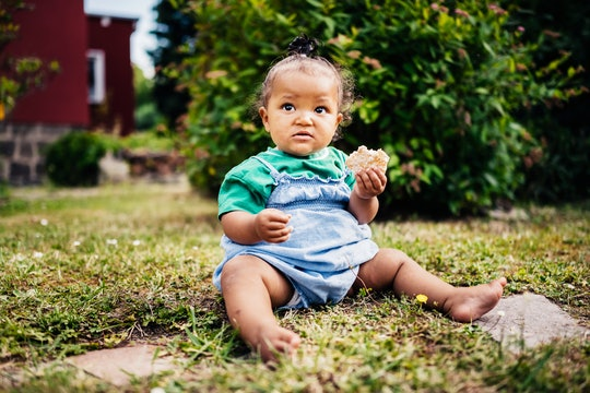 baby girl sitting in grass with snack
