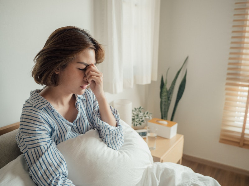 A woman holds her nose in bed wearing a striped pajama shirt. Recurring COVID symptoms take a toll for months, patients say.