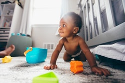 baby boy crawling on carpet in diaper