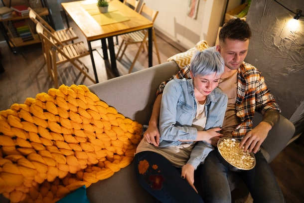 A cozy couple relaxes on the couch with popcorn, while watching a movie at home.