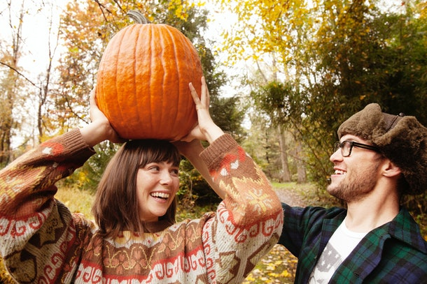 A young couple plays with a pumpkin in their backyard while wearing sweaters and a turkey hat.