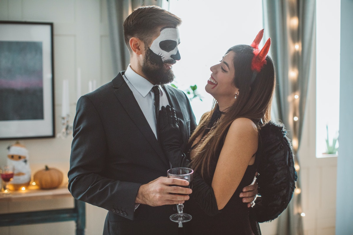 A couple dressed in Halloween costumes embrace while holding drinks.