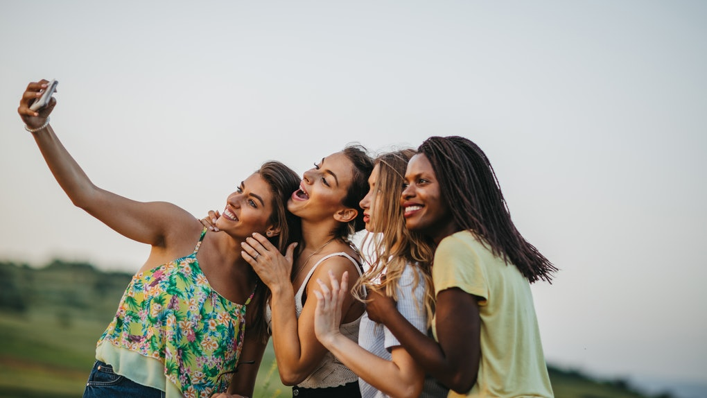 A group of women embrace while taking a selfie outside in a field.