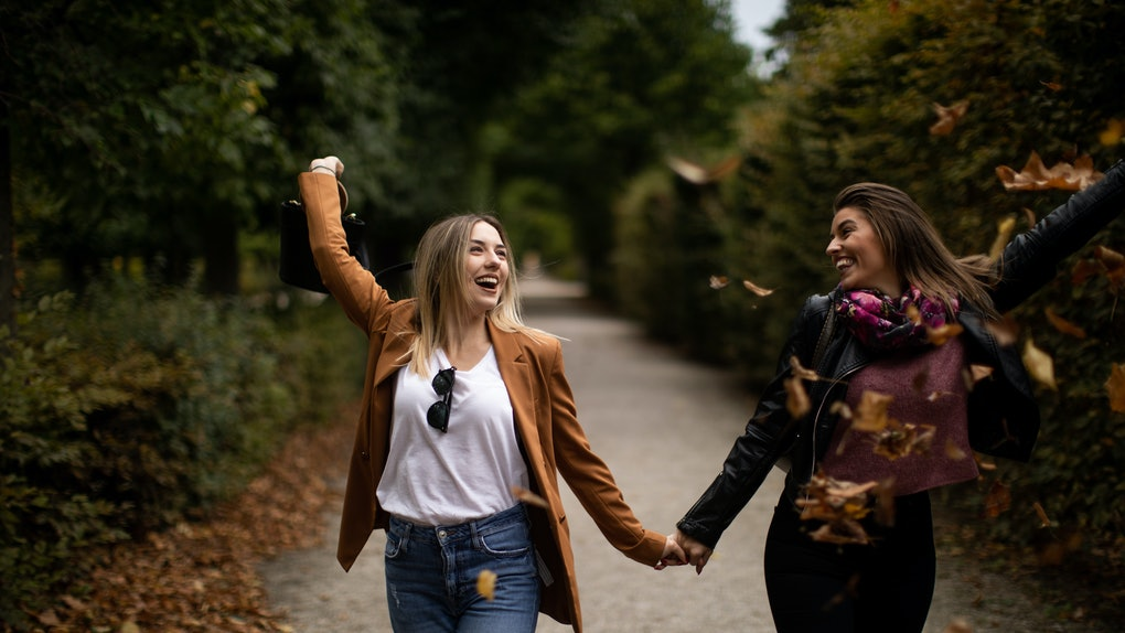 A young lesbian couple walks down a dirt path while holding hands and tossing fall leaves.