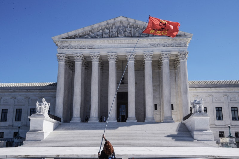 """The Supreme Court, with a person flying a """"Notorious RBG"""" flag. Law experts explain what could happen to Roe v. Wade after Ruth Bader Ginsburg's death."""
