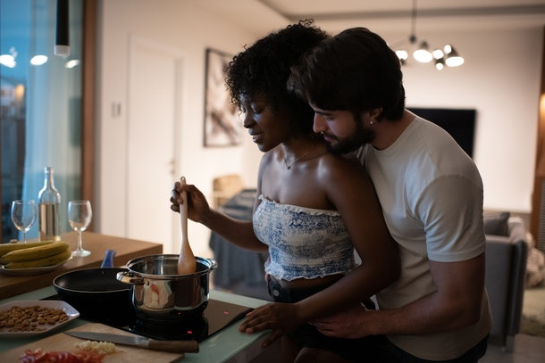A couple works together to cooking something in the kitchen.
