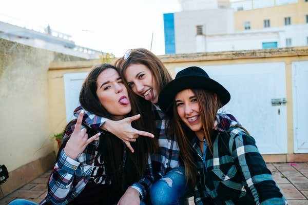 Three friends hang out and have fun on the roof, while wearing matching flannel shirts.