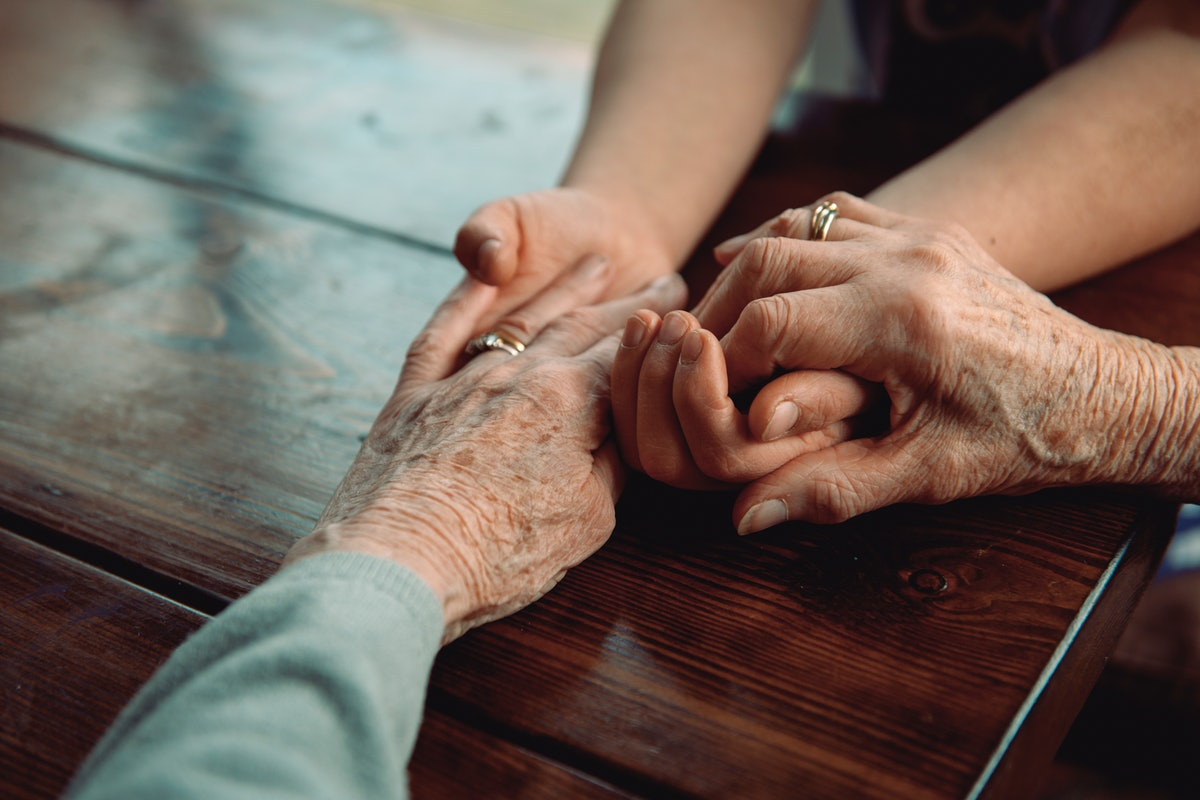 A granddaughter and grandmother hold hands. This article details Latinx Wellness Practices Passed Down From Abuelas