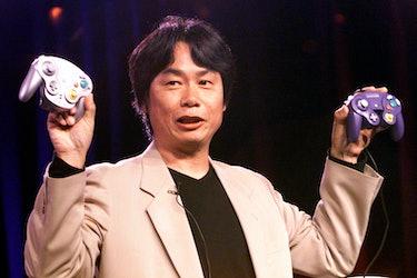 Miyamoto holding two GameCube controllers.