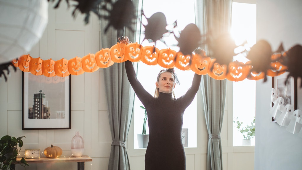 A woman hangs up a Halloween banner in her home.